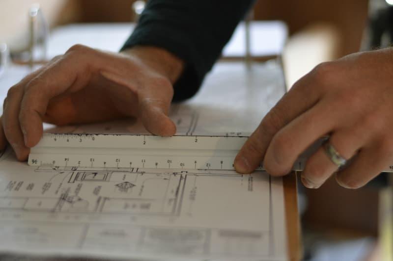 Contractor hands measuring plans