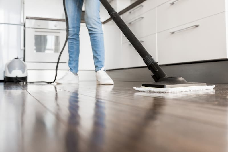 Woman cleaning textured tile floor with steam mop