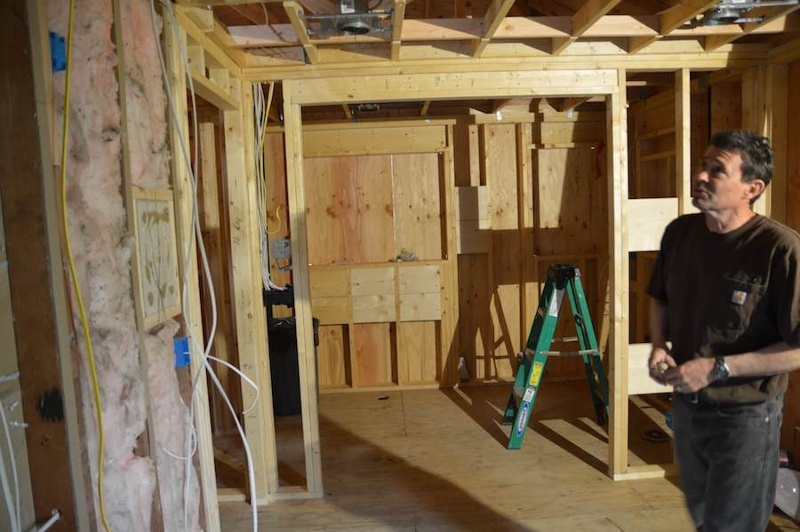 Carpenter looking at wood studs and insulation