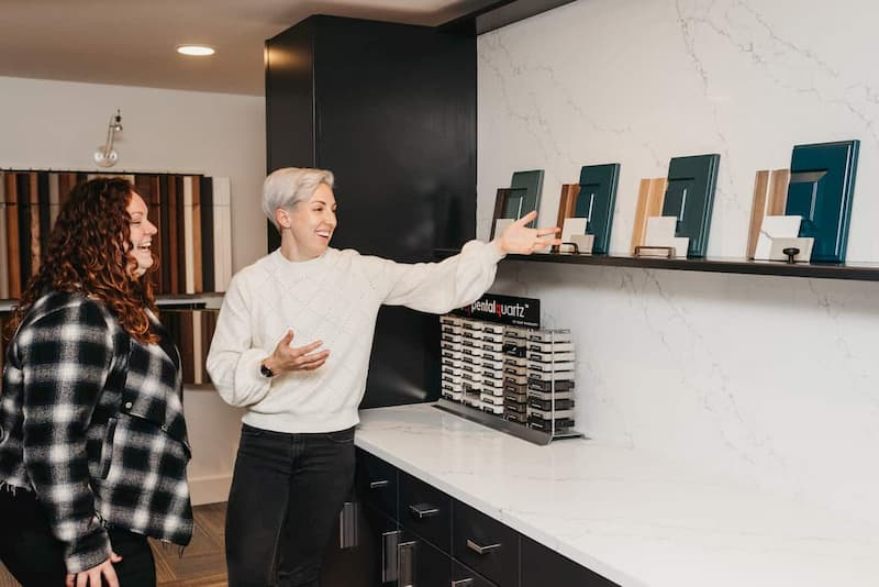Two women meeting to review kitchen details.