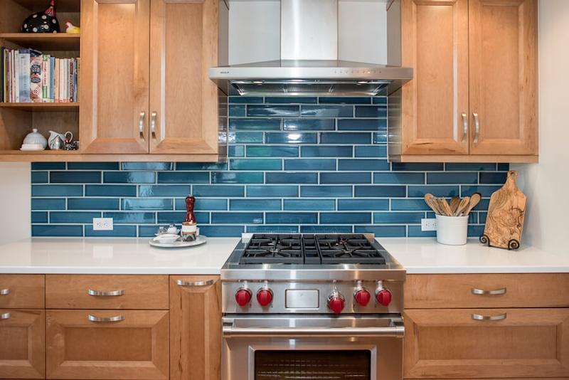 Stainless steel range with blue handmade tile backsplash