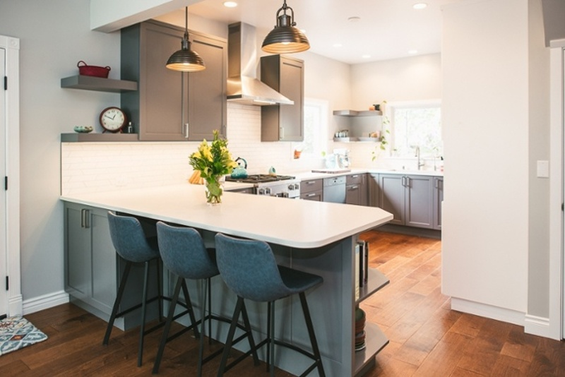 Remodeled kitchen with pendant lights over small countertop eating area